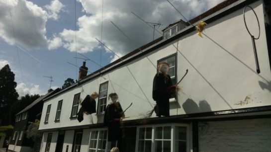 Harry Potter figures hanging from wires outside a cottage