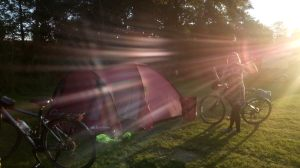 sunshine and a girl on a bike next to a tent