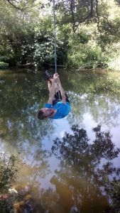 Guy on a rope swing over a river