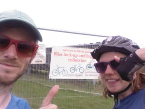 Two people in front of a Glasto sign