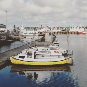 A small yellow boat in a harbour